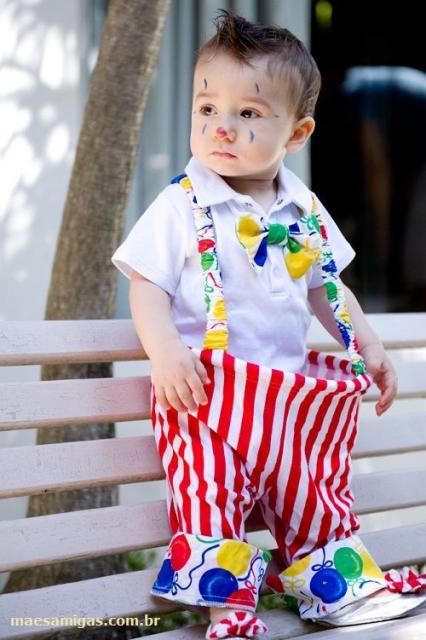 Bebê vestido de palhaço, com calça listrada de vermelho e branco.