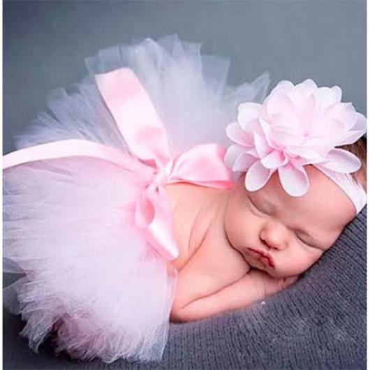 Bebê dormindo com adereço rosa na cabeça e saia de tutu rosa.