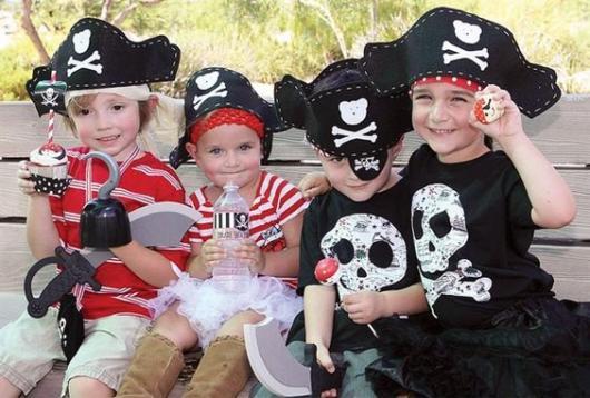 Quatro crianças vestidas de piratas, com roupas pretas e vermelhas.