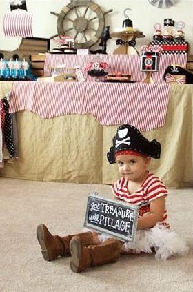 Menina vestida de pirata, com saia, blusa listrada e chapéu.