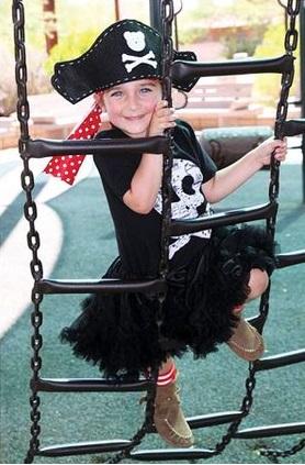 Menina vestida de pirata com blusa e saia pretas e chapéu.