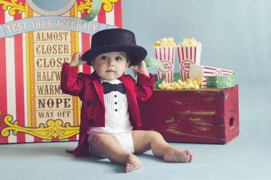Bebê vestido de mágico, com body branco, paleto vermelho e chapéu preto.