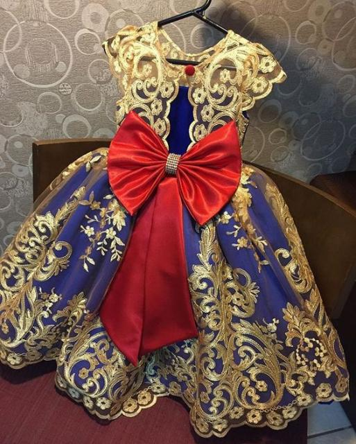 Vestido azul com detalhes dourados e laço vermelho na cintura.