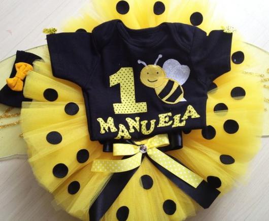 Fantasia de joaninha com camiseta preta e saia de tutu amarela com bolinhas pretas.