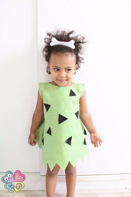 Menina vestida de Pedrita com roupa verde com detalhes marrons e adereço na cabeça.