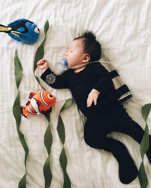 Criança vestida de mergulhador, com macacão preto e equipamento para mergulho.