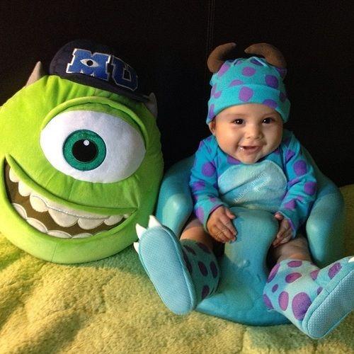 Criança vestida de Sulley, do Monstros S.A, ao lado de almofada do Mick Wazowski.