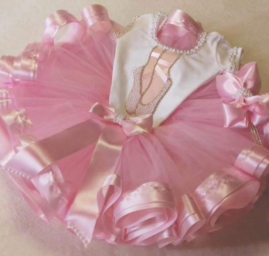 Roupa de bailarina, com saia rosa e blusa branca com desenho de sapatilhas.