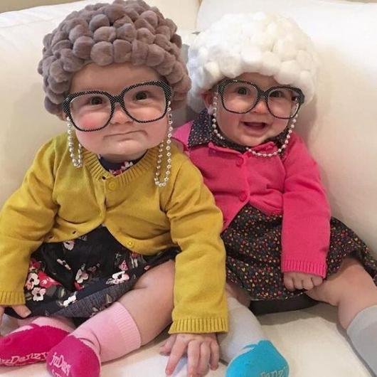 Dois bebês vestidas de idosas, com óculos.