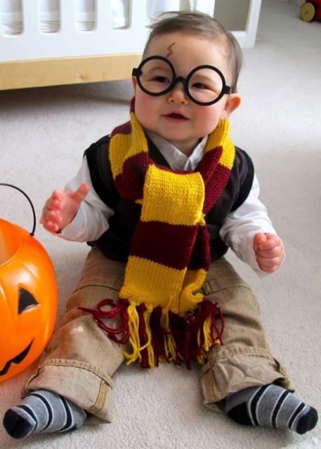 Menino vestido de Harry Potter, com cachecol amarelo e bordo, óculos e com maquiagem imitando a cicatriz do personagem.
