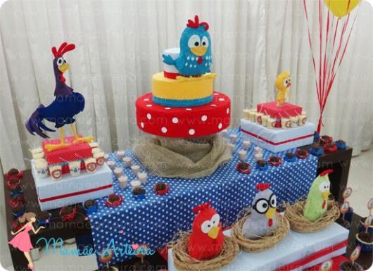 Mesa do bolo com toalha azul com bolinhas brancas e personagens da turma.