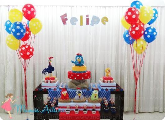 Decoração com cortina branca no fundo da mesa do bolo e balões coloridos.