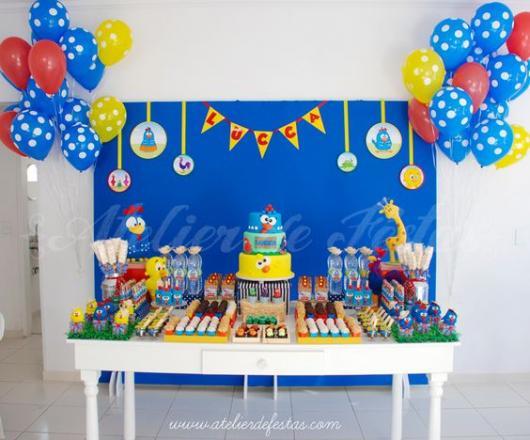 Mesa branca com bolo e docinhos.