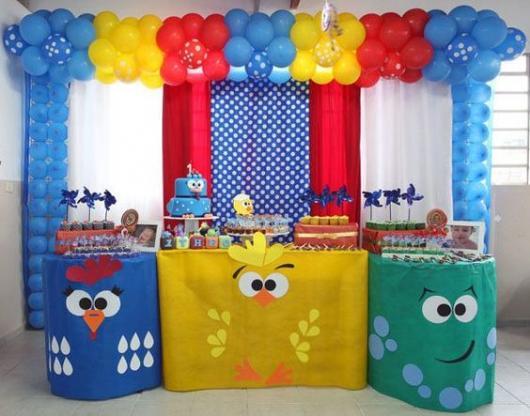 Mesa do bolo que três toalhas, uma da Galinha Pintadinha, uma do Pintinho e uma da Baratinha.