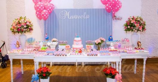 Festa com painel rosa e bexigas e itens decorativos rosas.