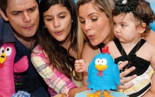 Flavia Alessandra, Otaviano Costa e filhas assoprando vela de bolo.