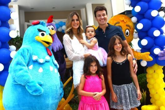 Rodrigo Faro e família posando em entrada de festa com personagens.