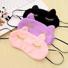 Três máscaras de dormir, uma rosa, uma lilás e uma preta.