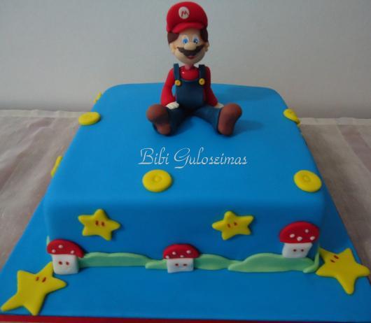 Bolo azul em pasta americana com boneco do Mario.