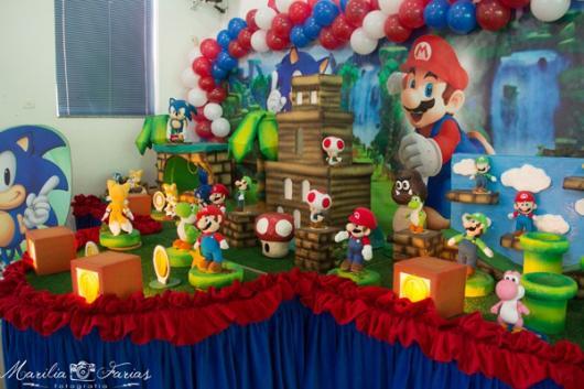 Mesa decorada com bonecos do Mario e do Luigi.