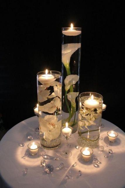 Enfeite com flores, copos e velas.