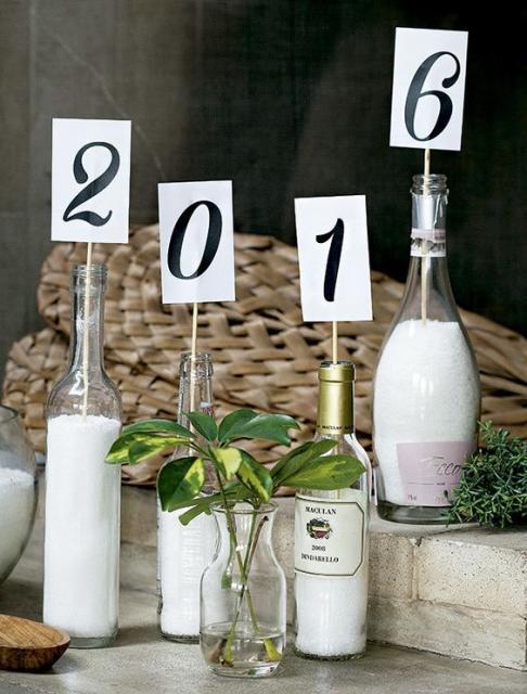 Garrafas servindo como vasos, com plaquinhas formando o novo ano.
