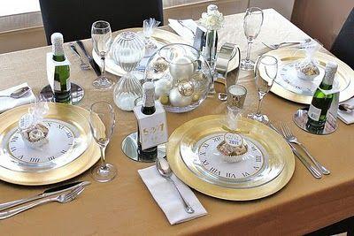 Mesa de jantar decorada com pratos transparentes e aparadores com desenho de relógio.