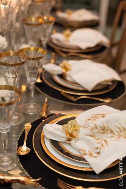 Mesa da ceia de Ano Novo com louça preta e dourada.