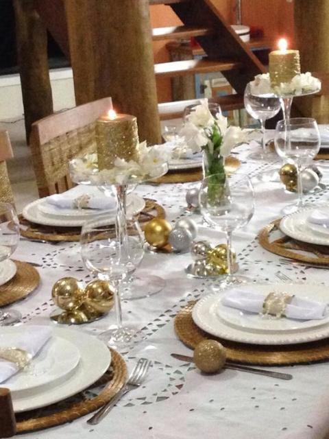 Mesa decorada para ceia de Ano Novo, com velas e flores.