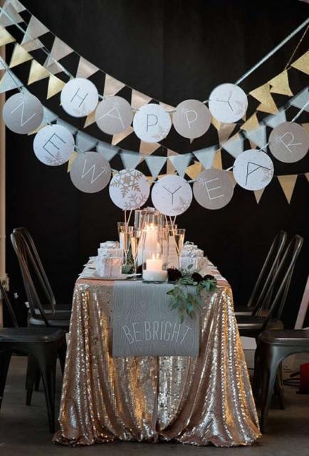 Mesa decorada com toalha dourada e bandeirinhas penduradas em cima.