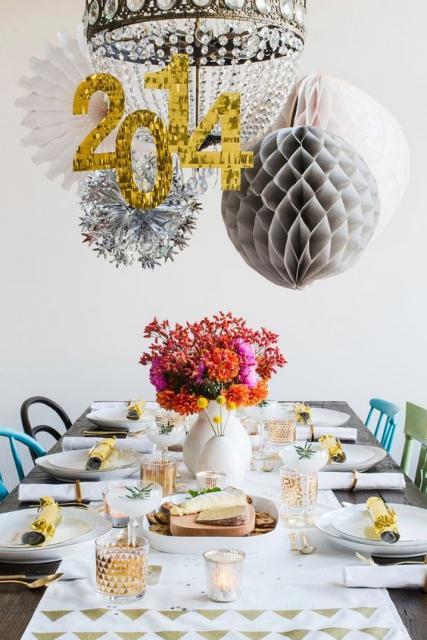Mesa decorada com itens brancos e balões pendurados.