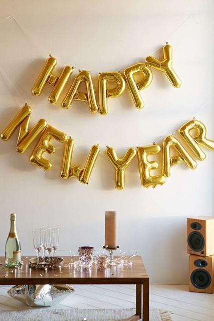 Decoração com balões de letras douradas formando a frase: Happy New Year.