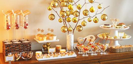 Mesa de comidas decorada com bolas douradas.