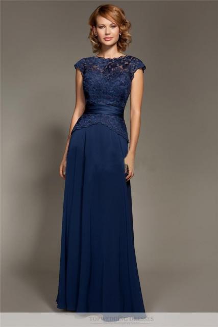 Modelo usa vestido azul escuro, modelo acinturado.