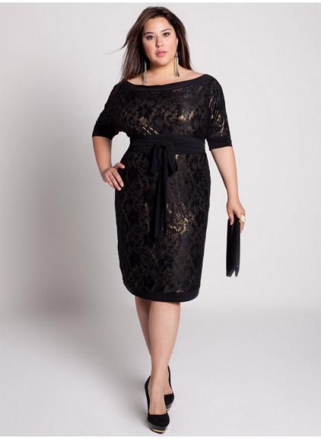 Modelo usa vestido e sapato preto com bolsa de mão na mesma cor.