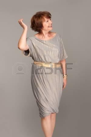 Modelo usa vestido curto, cinza de manguinhas curtas.