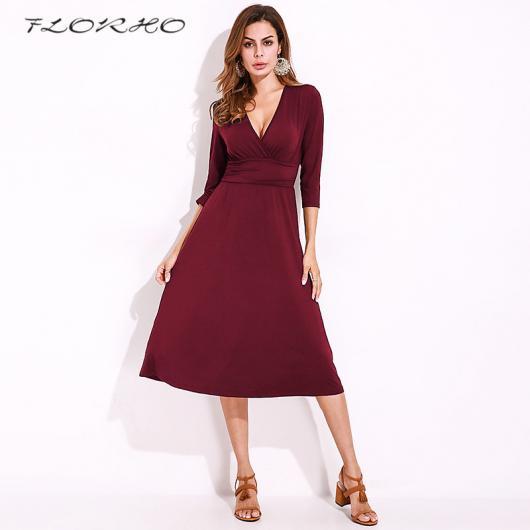 Modelo usa sandalia caramelo e vestido vermelho escuro com decote.