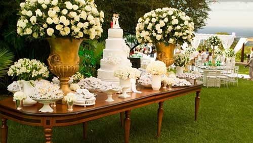 Decoração de Bodas de Ouro ao ar livre com mesa de madeira e muito verde