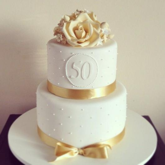 Bolo branco de 2 andares com detalhes de fita dourada e flores de açucar