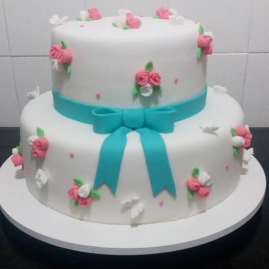 Bolo Jardim Encantado de pasta americana branca com laço azul e rosinhas