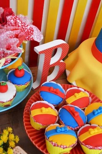 Cupcake Branca de Neve cute decorado com lacinhos amarelos e vermelhos