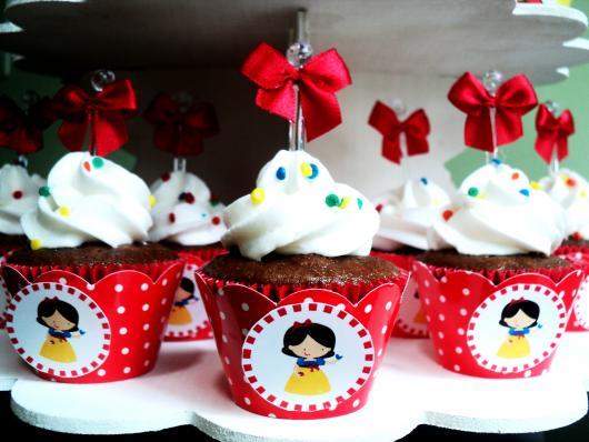 Cupcake Branca de Neve decorado com chantilly branco e lacinho vermelho