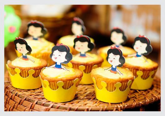 Cupcake Branca de Neve com wrapper amarelo e topper da Branca de Neve
