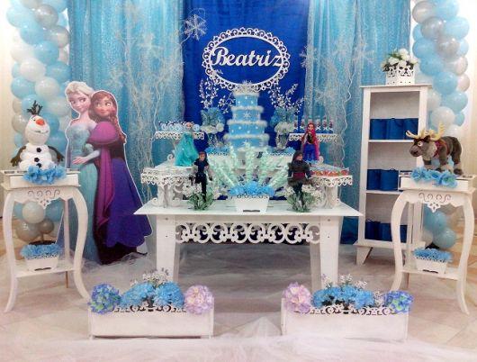 Festa Frozen provençal com cortina azul e branca e displays dos personagens