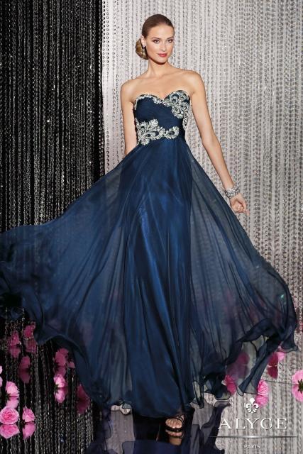 Modelo usa vestido azul escuro, tomara que caia com bordados no busto.