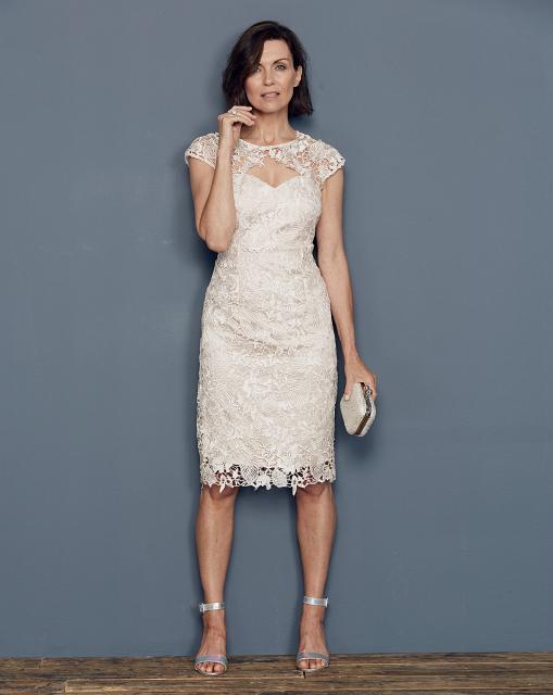 Modelo veste vestido branco de renda com sandalia branca.