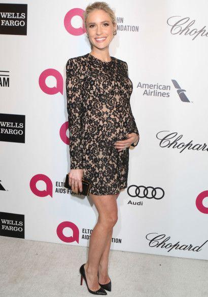 Modelo usa vestido preto de bordados com clutch pequena e sapato.