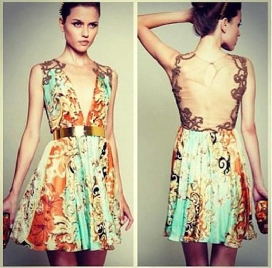Modelo usa vestido estampado nas cores, verde,laranja e amarelo claro com cinto dourado.