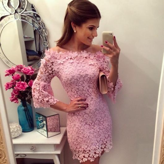 Modelo usa vestido rosa manga longa, sem decote em renda.