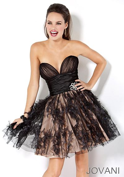 Modelo usa vestido preto tomara que caia com saia bufante.